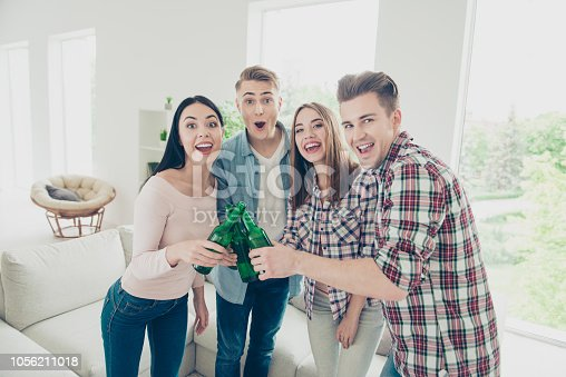 istock Carefree, group of four youngster, youth people with beer bottles in their hands looking into the camera with big toothy smile 1056211018