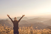 Carefree Happy Woman Enjoying Nature on grass meadow on top of mountain cliff with sunrise. Beauty Girl Outdoor. Freedom