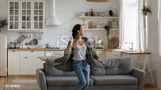 istock Carefree happy young woman dancing alone in modern kitchen 1191083832