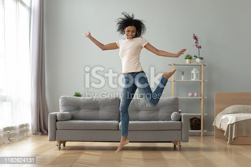 Carefree joyful african american millennial girl jumping dancing alone at home, happy funky active young fit mixed race woman having fun laughing flying in air in studio apartment room interior