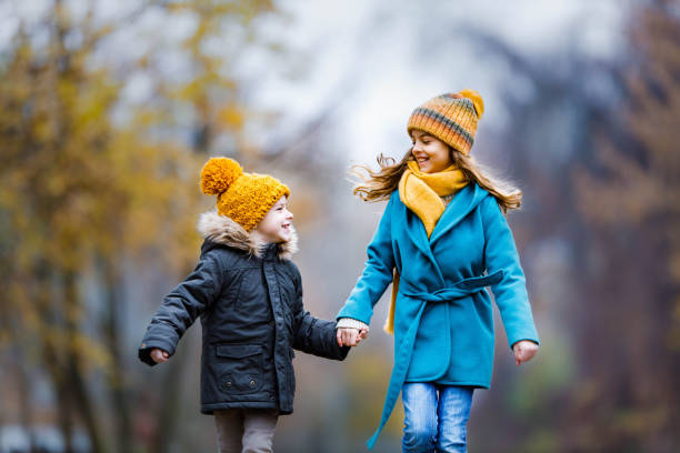 Carefree kids running in autumn day at the park. stock photo