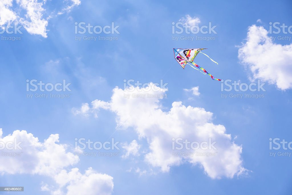 Carefree kite flyes in the blue sky stock photo