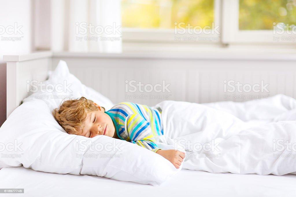 carefree little kid boy sleeping in bed in colorful nightwear. – Foto