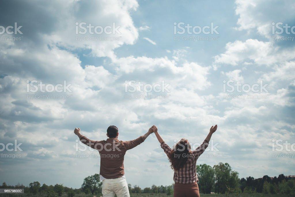 Zorgeloze man en vrouw verhogen handen aan de hemel - Royalty-free Alleen volwassenen Stockfoto