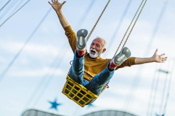 Carefree olgun adam eğlence parkı zincir salıncak binmek eğlenmek. stok fotoğrafı