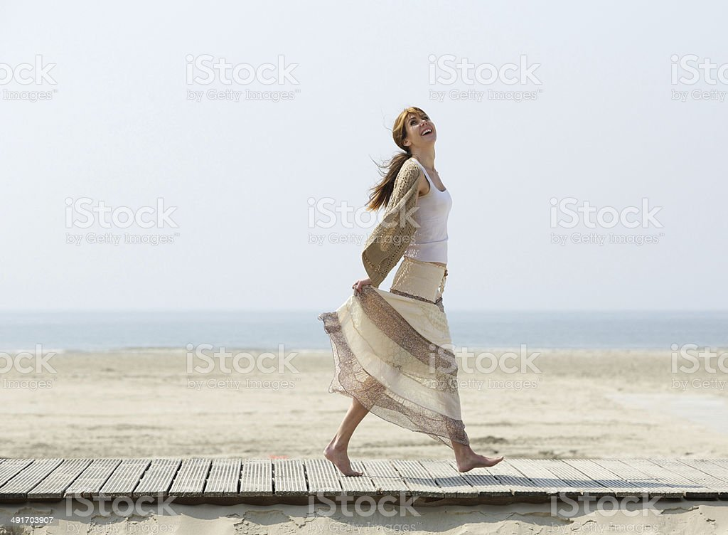 Carefree mature woman walking barefoot at beach stock photo