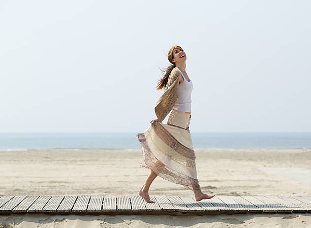 Carefree mature woman walking barefoot at beach stock photo