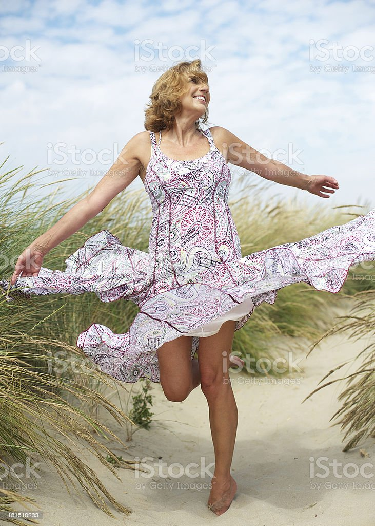 Carefree middle aged woman dancing outdoors stock photo