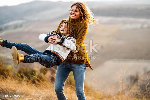 Young happy mother having fun while spinning her little daughter in autumn day on a hill. Copy space.