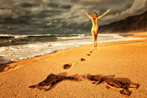 Carefree Nude Woman Walking On Beach At Sunset Stock Photo