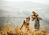 Young happy family talking while having fun in autumn day outdoors. Father is carrying son on shoulders while mother is piggybacking daughter. Copy space.