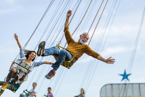 carefree people having fun on chain swing ride in amusement park. - balouço imagens e fotografias de stock