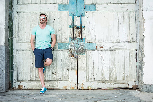 Carefree Handsome man posing on the wooden doors shorts stock pictures, royalty-free photos & images