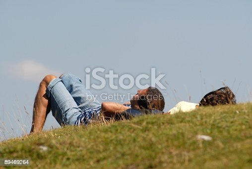 Break. Looking to the sky. Carefree relax, leisure. Couple lying on the grass and watching  sky.