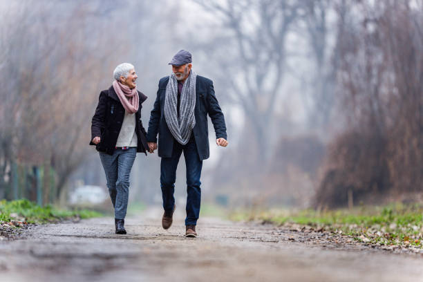 Carefree senior couple having fun in winter day at the park. stock photo