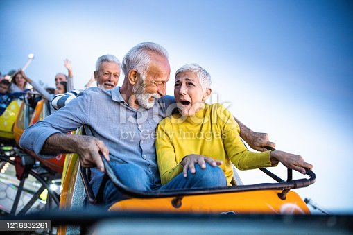 Senior couple having fun while riding on rollercoaster at amusement park. Woman is scared.