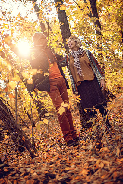 carefree senior couple singing during autumn day in the forest. - full length of senior people singing together against white stock photos and pictures