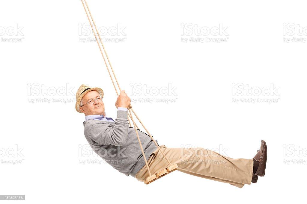Carefree senior man swinging on a wooden swing stock photo