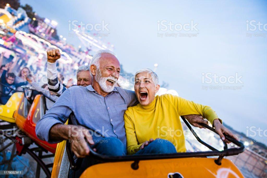 Carefree seniors having fun on rollercoaster at amusement park. Cheerful senior couple having fun while riding on rollercoaster at amusement park. Copy space. Active Seniors Stock Photo