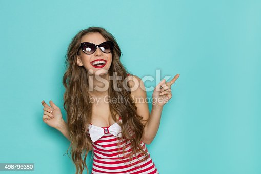 Laughing sexy young woman in sunglasses, red striped shirt with cleavage. Three quarter length studio shot on teal background.