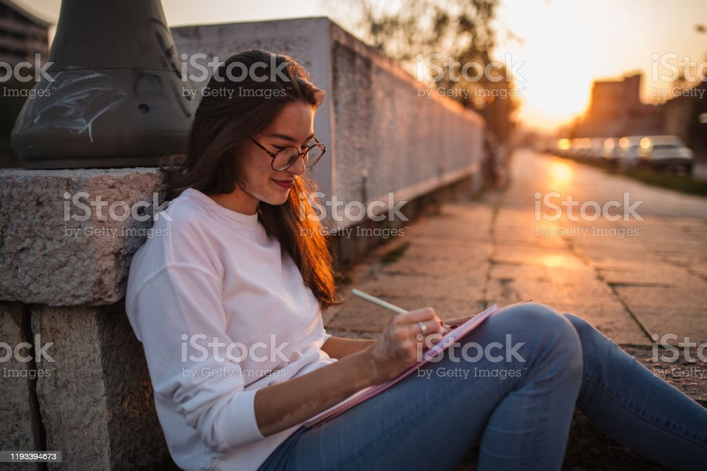 Carefree student drawing Art student drawing in her notebook while relaxing on stone stairs Adolescence Stock Photo