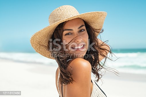 Portrait of beautiful smiling young woman wearing straw hat at beach with sea in background. Beauty fashion girl looking at camera at seaside with big grin. Carefree tanned woman walking on sand and laughing.