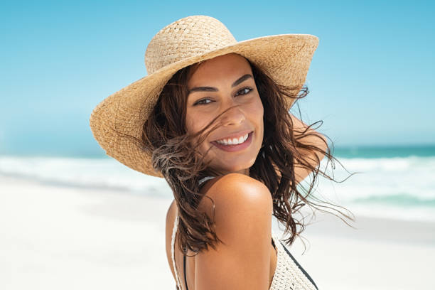 Carefree stylish woman enjoying summer Portrait of beautiful smiling young woman wearing straw hat at beach with sea in background. Beauty fashion girl looking at camera at seaside with big grin. Carefree tanned woman walking on sand and laughing. beautiful woman stock pictures, royalty-free photos & images