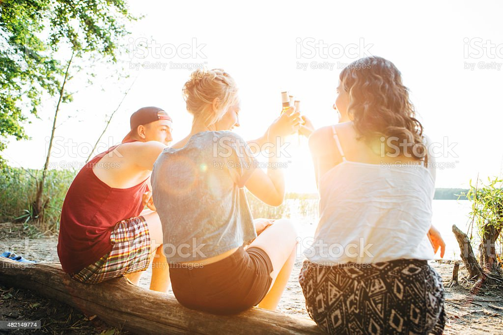 carefree summer day: Friends toast with Beer At a Lake royalty-free stock photo