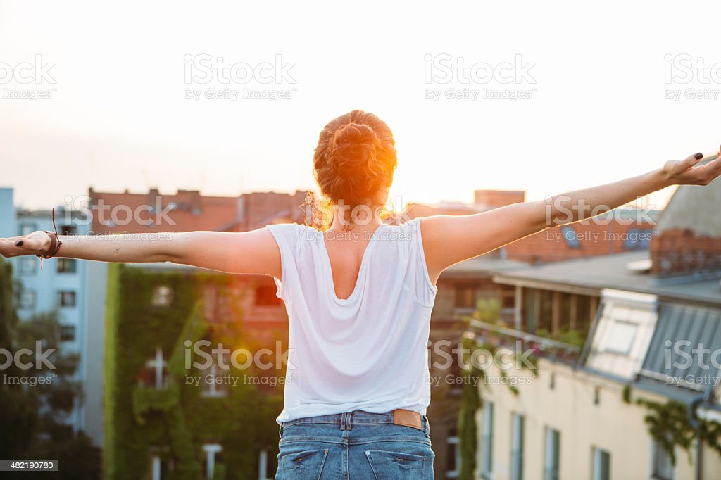 carefree summer day: rear view of young woman, feeling free stock photo