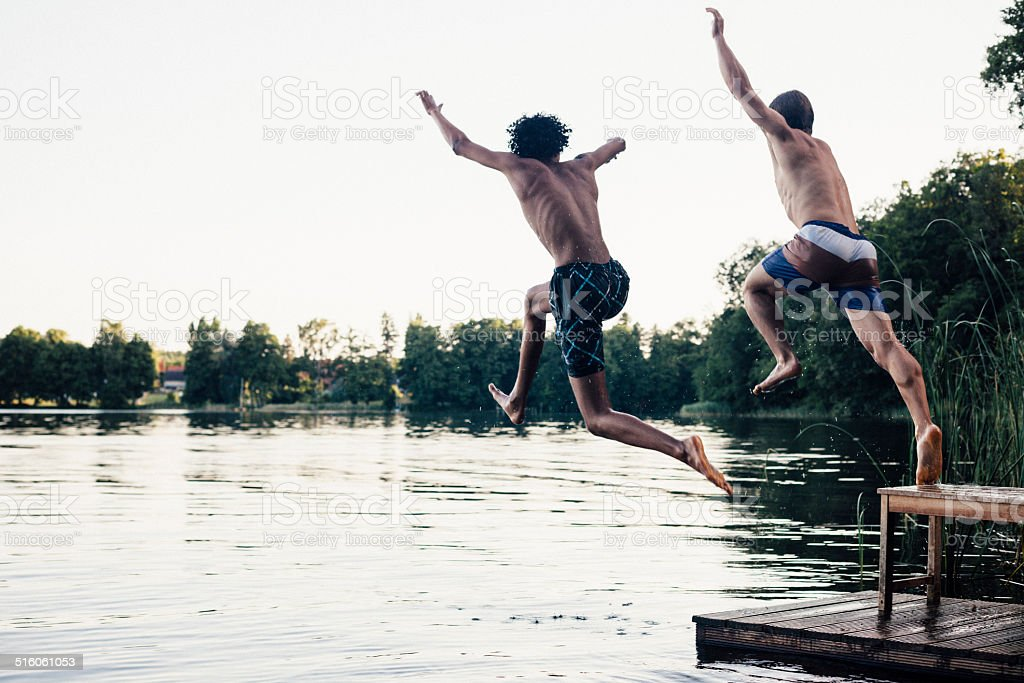 carefree summer day: teenagers jumping into a lake stock photo