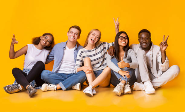 Carefree teenagers having fun over yellow studio background stock photo