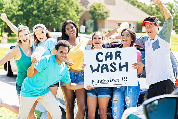 Carefree teenagers organize charity car wash stock photo