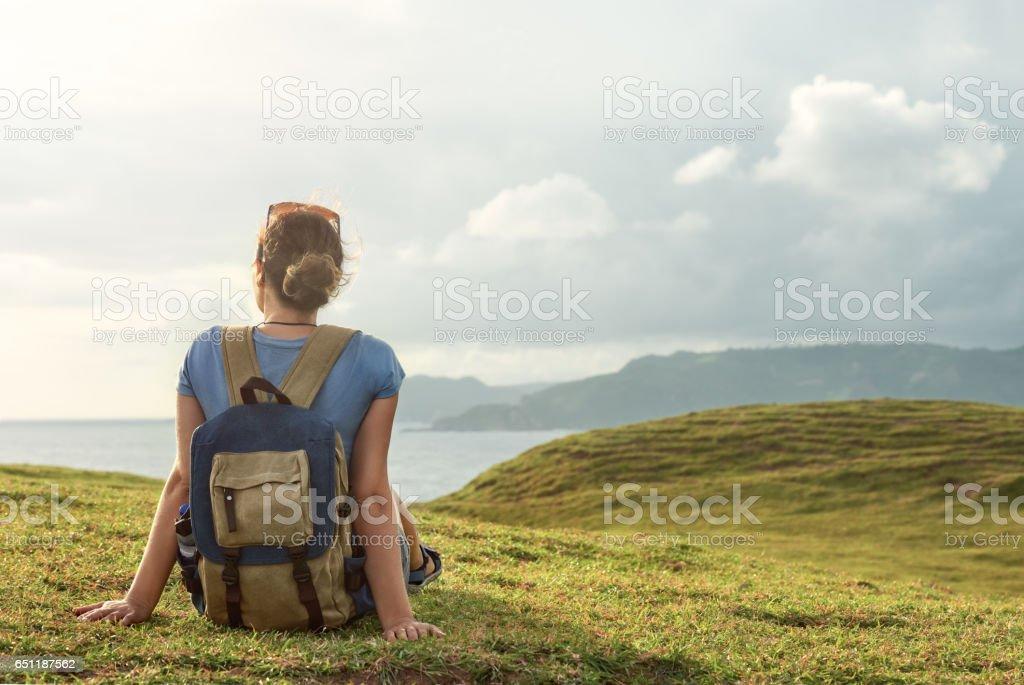 carefree traveller with backpack enjoying sunset on peak of mountain. stock photo