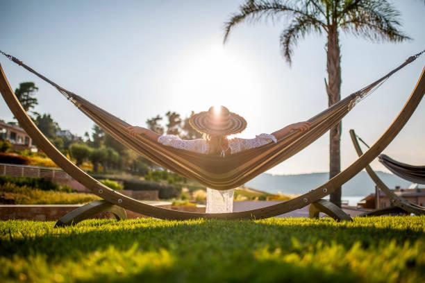 unbeschwerte frau genießen in einem luxus-resort - sun chair stock-fotos und bilder