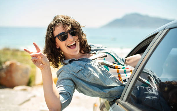Carefree woman hanging out of a car window during a beach road trip stock photo