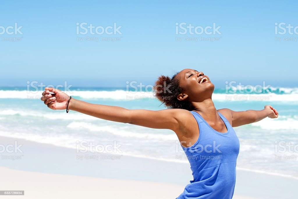Carefree woman having a good time at beach stock photo