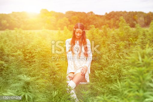 Carefree woman in cannabis field adjusting stockings