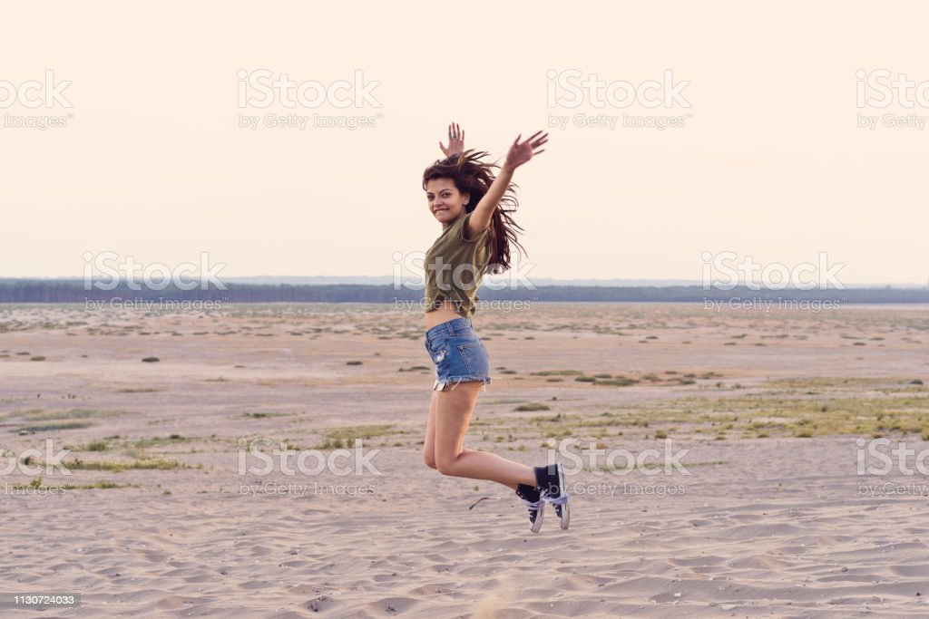 Carefree woman jumping at desert Portrait of carefree woman jumping at desert. Confident hipster is with arms raised in mid-air. She is enjoying her vacation during summer. 25-29 Years Stock Photo
