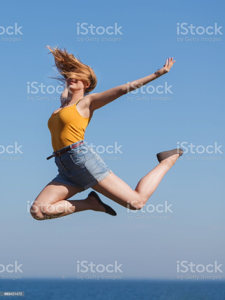 Carefree woman jumping by sea ocean water. stock photo