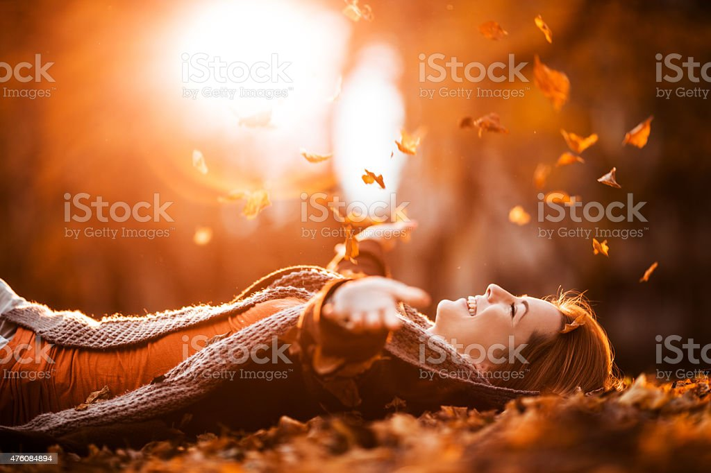 Carefree woman relaxing and throwing autumn leaves in nature. stock photo