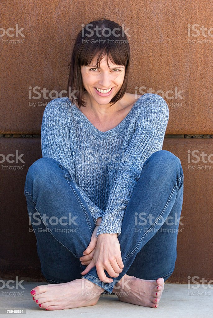 Carefree woman sitting and smiling stock photo