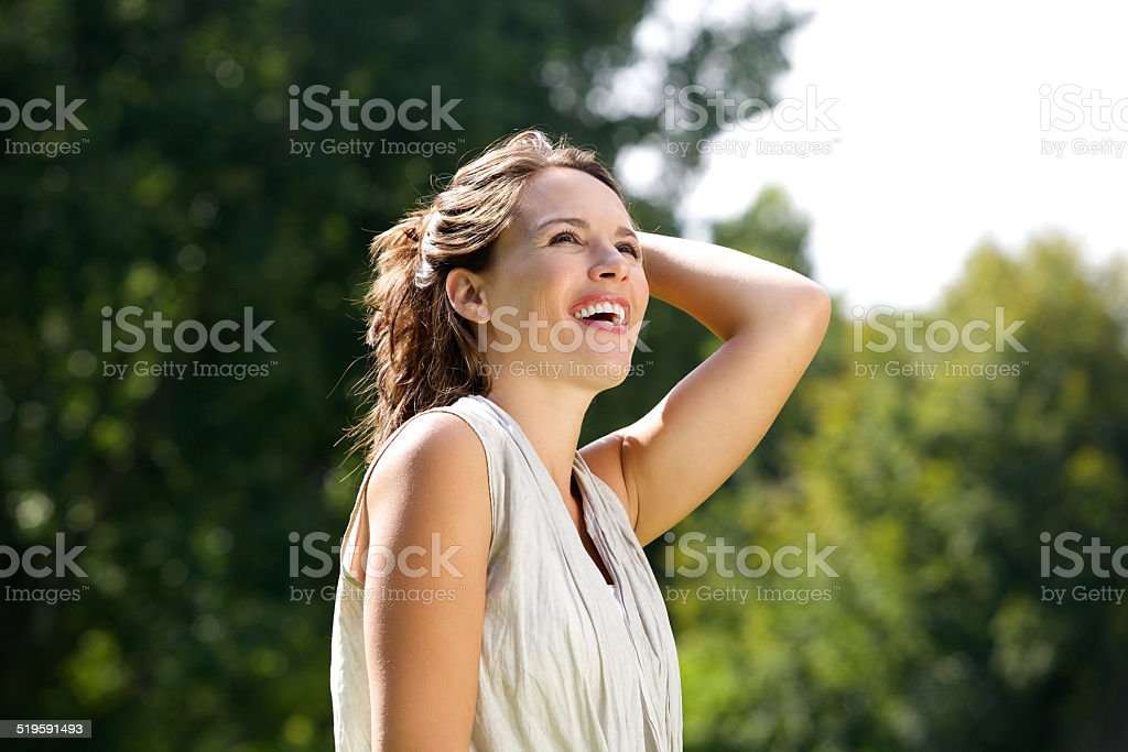 Carefree woman smiling with hand in hair outdoors stock photo