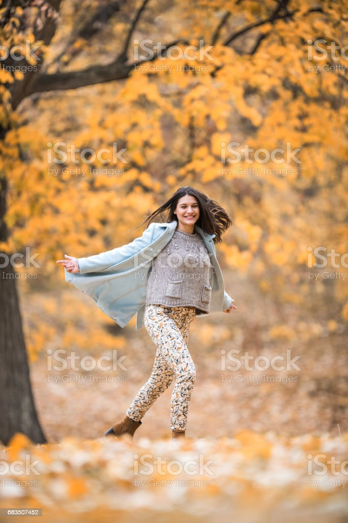 Carefree woman spinning and enjoying in autumn day outdoors. stock photo