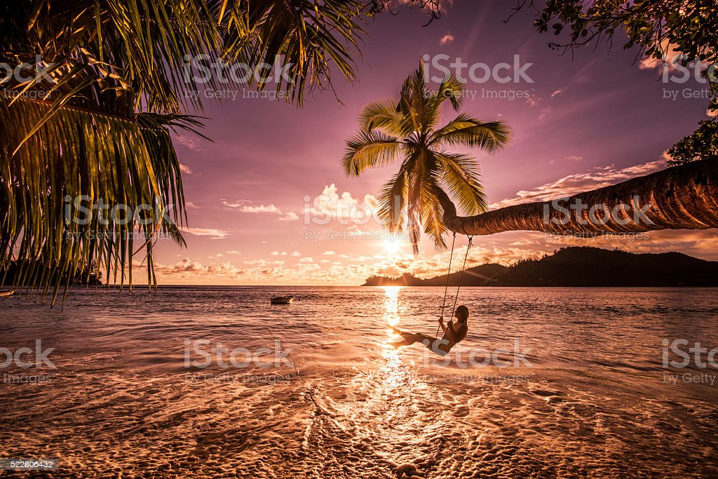 Carefree woman swinging above the sea at sunset beach. stock photo