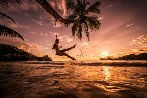 Carefree woman swinging above the sea at sunset beach.