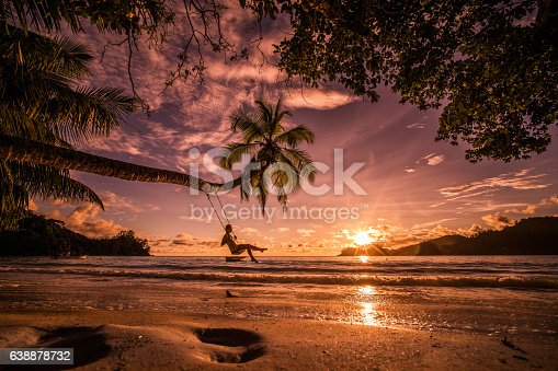 Young happy woman enjoying in beautiful sunset on the beach while swinging above the water.