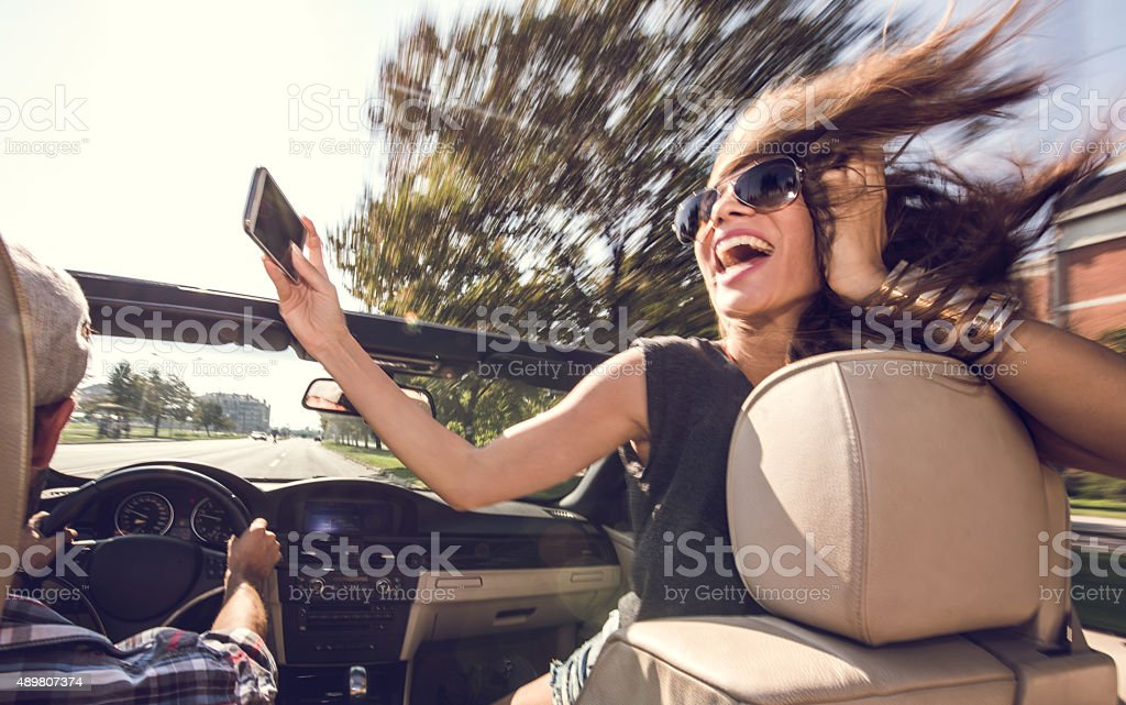 Carefree woman taking a selfie while driving in convertible car. stock photo