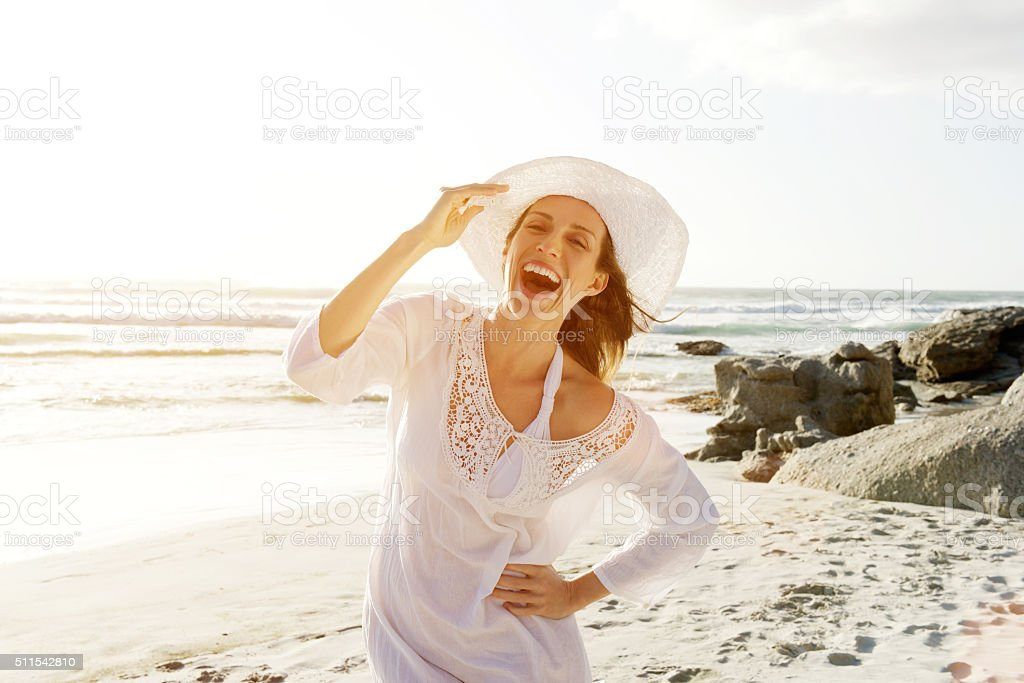 Carefree woman walking on beach with sun dress and hat stock photo