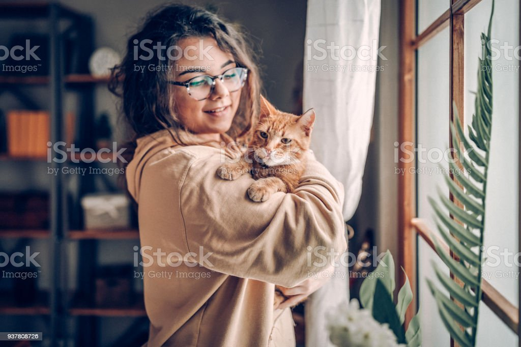 Young woman holding cat