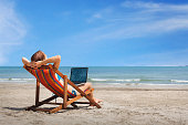 happy woman with laptop on the beach